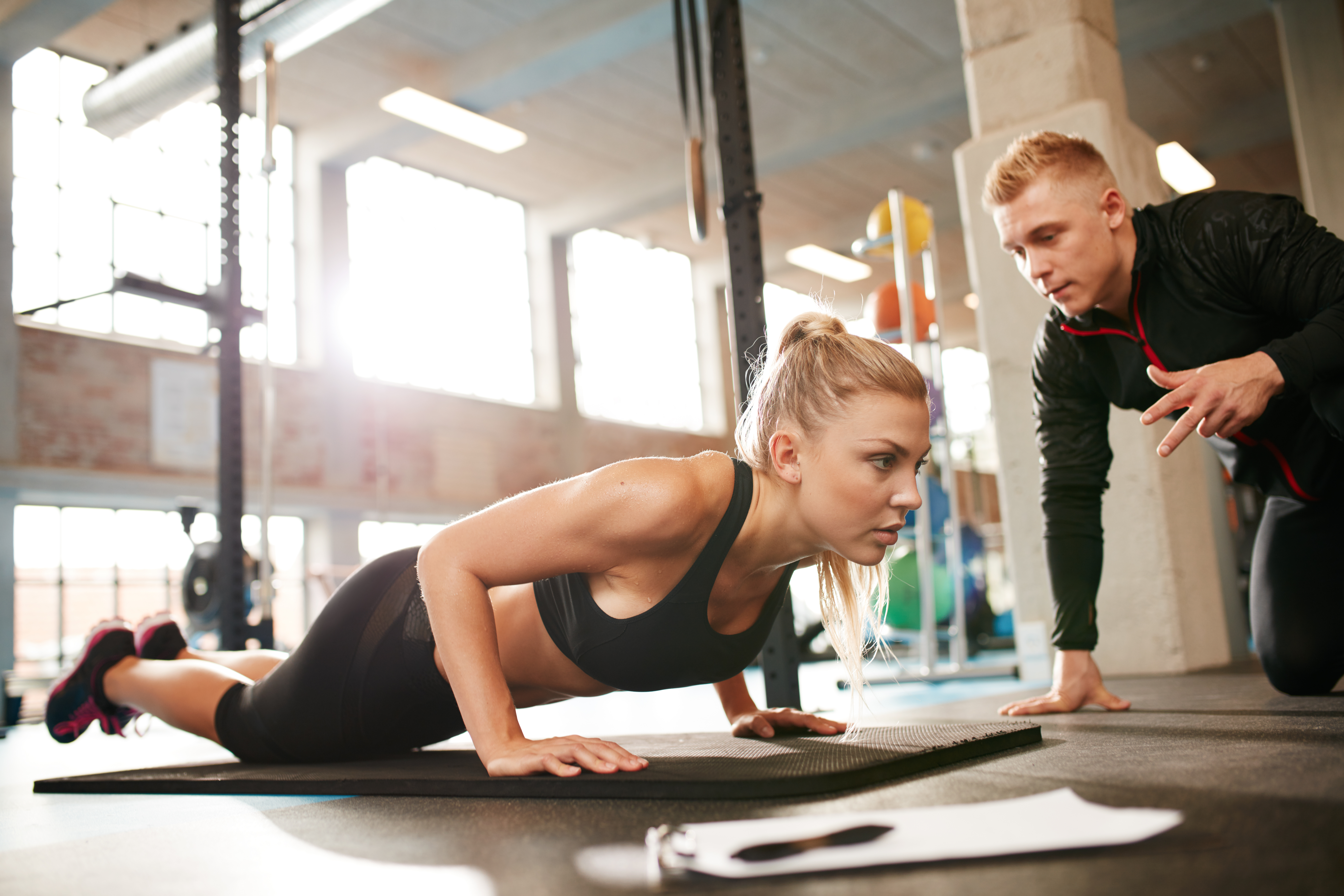 female-exercising-with-personal-trainer-at-gym-PSDYQTU